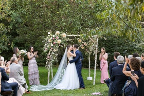 wedding ceremony green lawn birch four post ceremony structure pink greenery white flowers