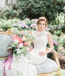 bohemian inspired bride sits on vintage blue settee Jinza Couture Bridal wedding dress