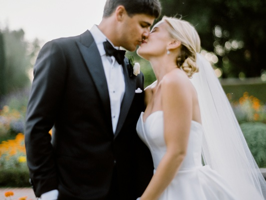 bride in sweetheart neckline gown, groom in tuxedo, bride and groom sharing kiss after first look