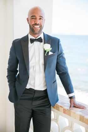 groom on balcony in mexico in blue and black tuxedo with bow tie