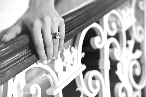 Black and white photo of bride's hand on staircase railing with halo engagement ring