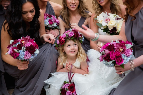 Bridesmaids in grey dresses surrounding flower girl with flower crown