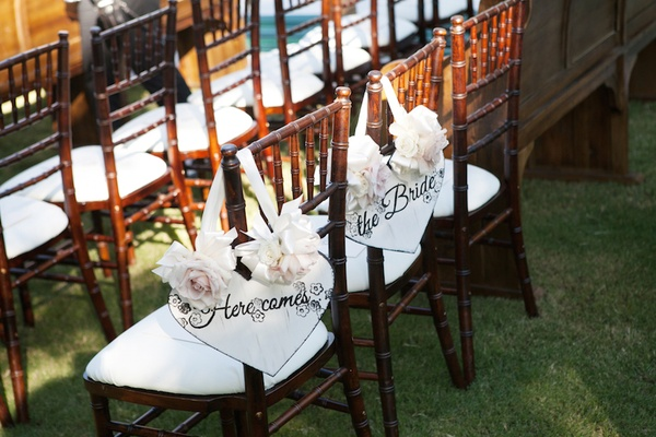 Wood ceremony chairs with white cushions and shabby chic signs