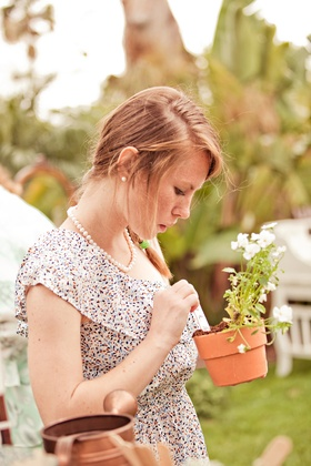 Girl looks at plant in pot