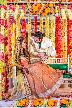 Indian bride and groom amid vibrant flower garlands