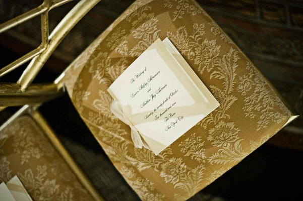 Simple ceremony booklet on gold embroidered chair