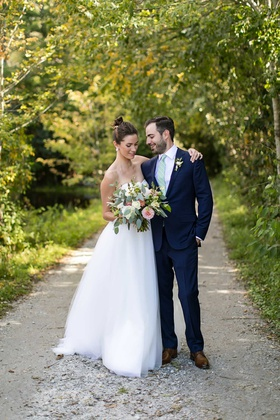wedding portrait bride in strapless wedding dress high bun bouquet groom in suit with light green ti