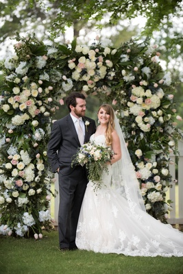 bride in lace mermaid gown, groom in charcoal suit at floral arch