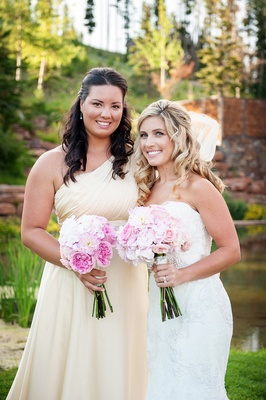 Bride in strapless Watters gown with bridesmaid in Vera Wang one shoulder bridesmaid dress