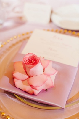 place setting with lavender napkin, pink rose, and charger with gold rim