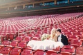 Bride and groom in stadium chairs at Busch Stadium in St. Louis in wedding dress and tuxedo