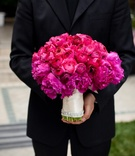 Groom holding peony flowers wrapped in ribbon