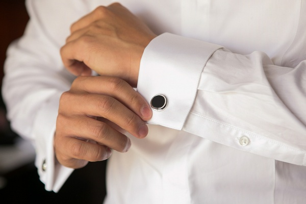 Black circular cufflinks for groom at wedding with silver border