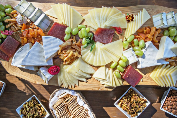 Wedding cheese plate crackers cheeses fruit meat charcuterie display on wood board reception