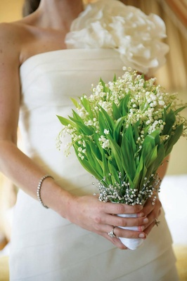 Bride in wedding dress holding lilies of the valley