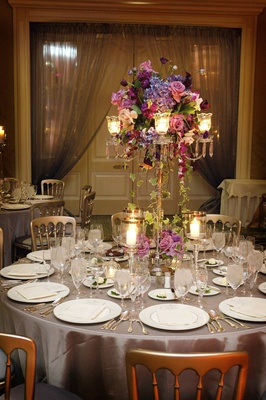 Wedding reception centerpiece in a silver candelabra with purple and fuchsia flowers