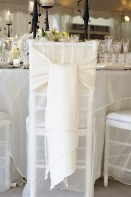 White fabric on back of chair tied into loose bow