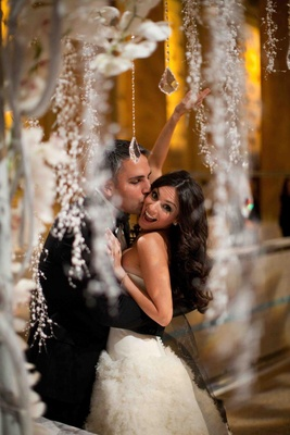 Groom hugs and kisses bride under crystal chuppah