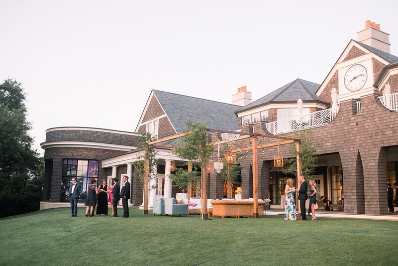 country club wedding outdoor lounge area with wooden structure and greenery