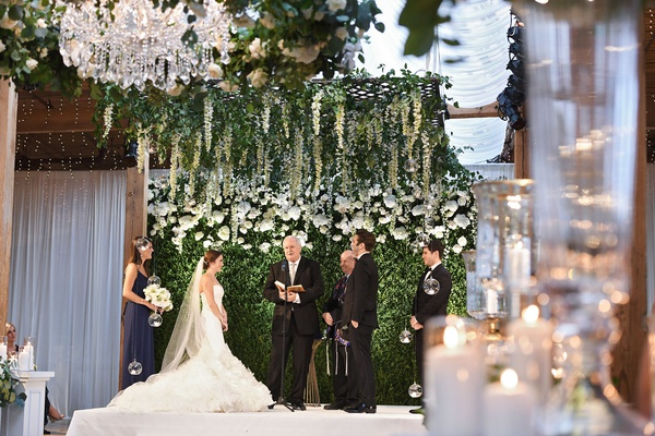 wedding ceremony green hedge wall wisteria chuppah chandelier officiant father of bride