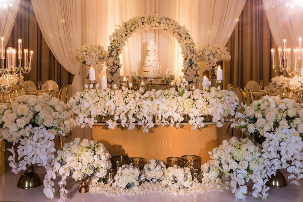 Sweetheart table in front of cake table with hundreds of white flowers on floor and table as decor