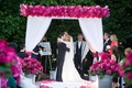 White drapery on chuppah with hot pink flowers