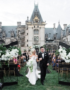 Bride in strapless mermaid gown and groom in tuxedo bouquet walking up aisle through gates chateau