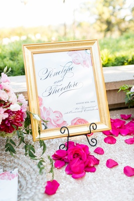 Wedding anniversary and vow renewal sign with pink roses and gold frame sequin table