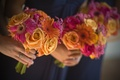 Bridesmaids carrying pink and orange nosegays
