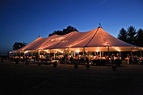 Farm wedding reception in an open-sided tent lit by market lights at sunset