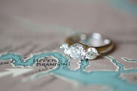 Bride's wedding ring three round diamonds on yellow gold band on map of venue area