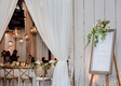 wedding reception in barn drapery orb pendants framed welcome sign with greenery white pink flowers