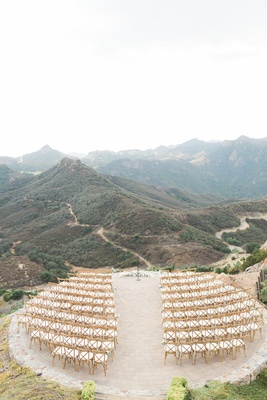 Wedding ceremony on helipad at vineyard estate in Malibu wood white chairs flowers at altar mountain