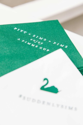 White cocktail napkin with green swan and hashtag and green signature cocktail napkin