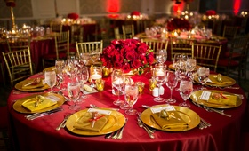 red linens, gold chiavari chairs, gold chargers, red roses