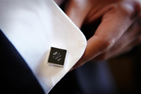 Groom wearing black and silver cufflink on shirt cuff
