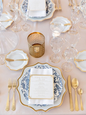 antique blue china on gold-rimmed charger with fold flatware on blush linens
