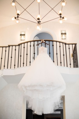 monique lhuillier ball gown with lace and tulle on hanger hanging from balcony before staircase