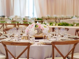 Rustic wedding wood chair round reception table with low centerpiece arrangement in gold vessel pink