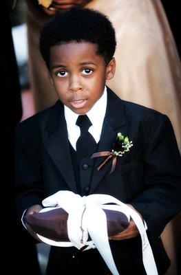 Ring bearer holds brown ring bearer pillow with white ribbon