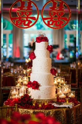 five tier cake with scrollwork and quilted pattern, red roses