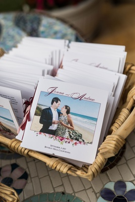 basket filled with ceremony programs for outdoor wedding photo of bride and groom at beach