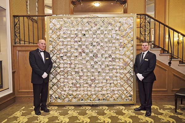 attendants by wall of escort card display on florals with gold hatching