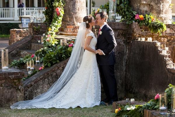 Bride kisses groom cathedral length veil Romona Keveza cap sleeve wedding dress outdoor wedding