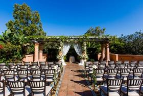 wedding ceremony outdoors tile floor trellis greenery white chuppah