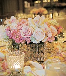 Small wedding reception centerpiece of roses, orchids, and hydrangeas
