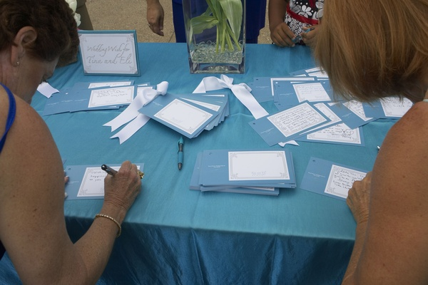 guests sign blue and white cards for the newlyweds
