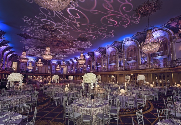 Silver chairs with purple cushions and tall ivory centerpieces with scroll gobo on ceiling