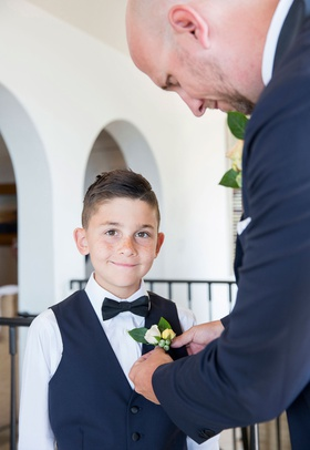 wedding ceremony ring bearer with vest and bow tie boutonniere being put on by groom new step dad