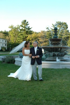 Bride and groom on grass lawn in front of fountain